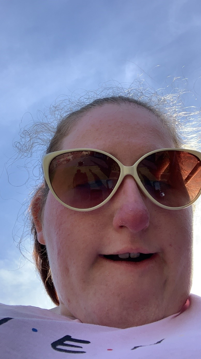 A selfie of Greer wearing sunglasses with a blue sky behind her