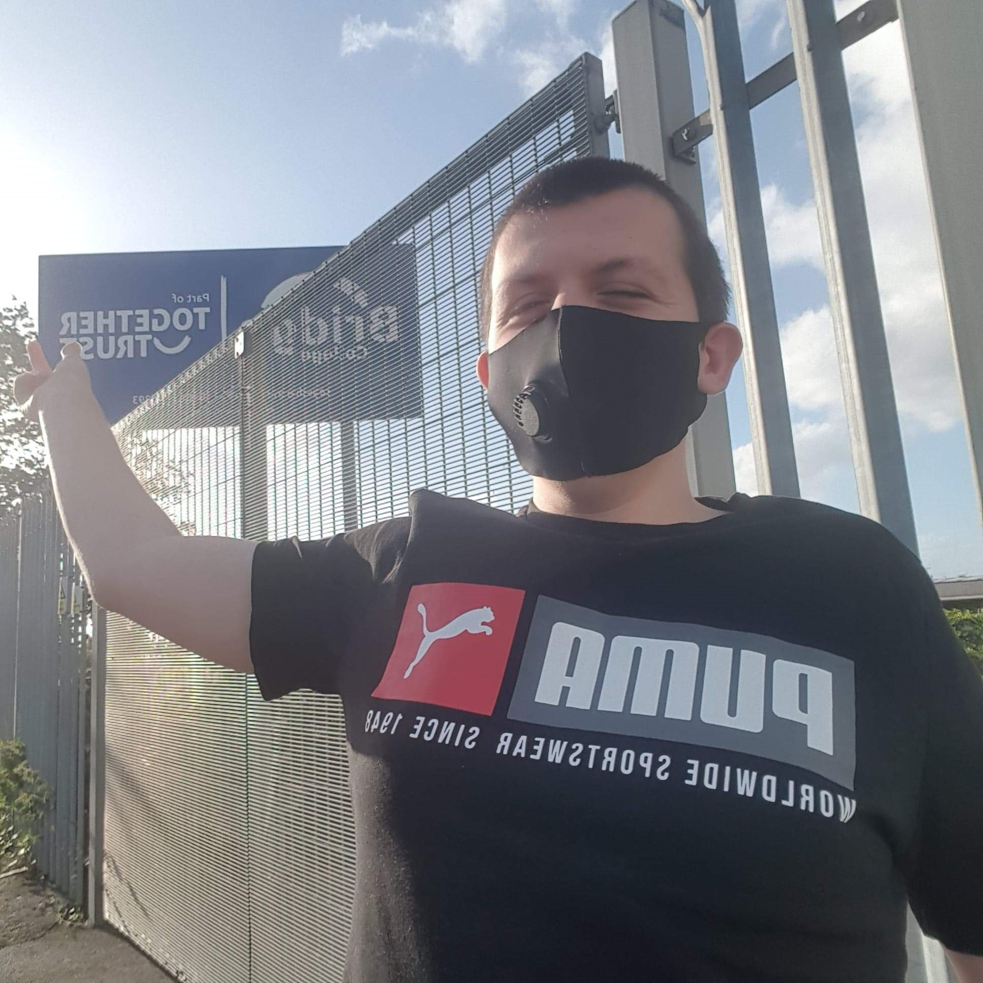 A photo of Liam outside Bridge College pointing at the sign. He is wearing a face mask.