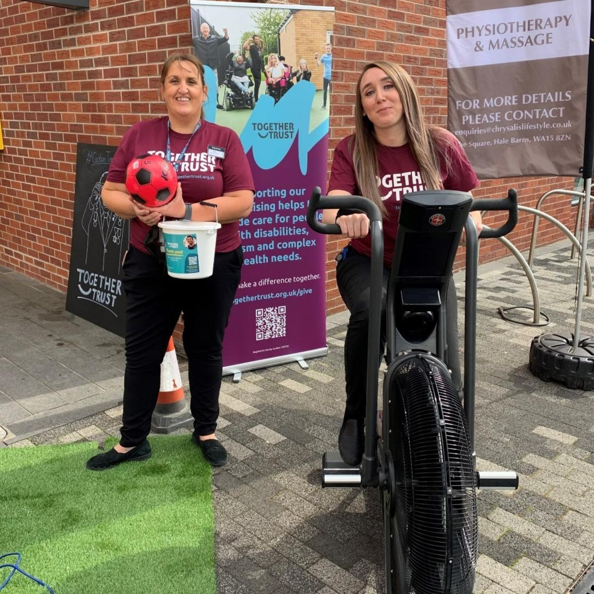 A team member from Booths holding a collection bucket next to another sat on an exercise bike