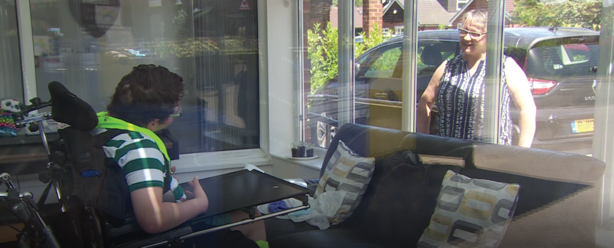 Ben talking to his mum through a window