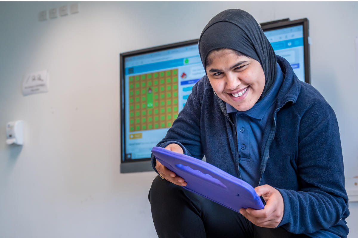 A Bridge College student with an ipad, enjoying school time