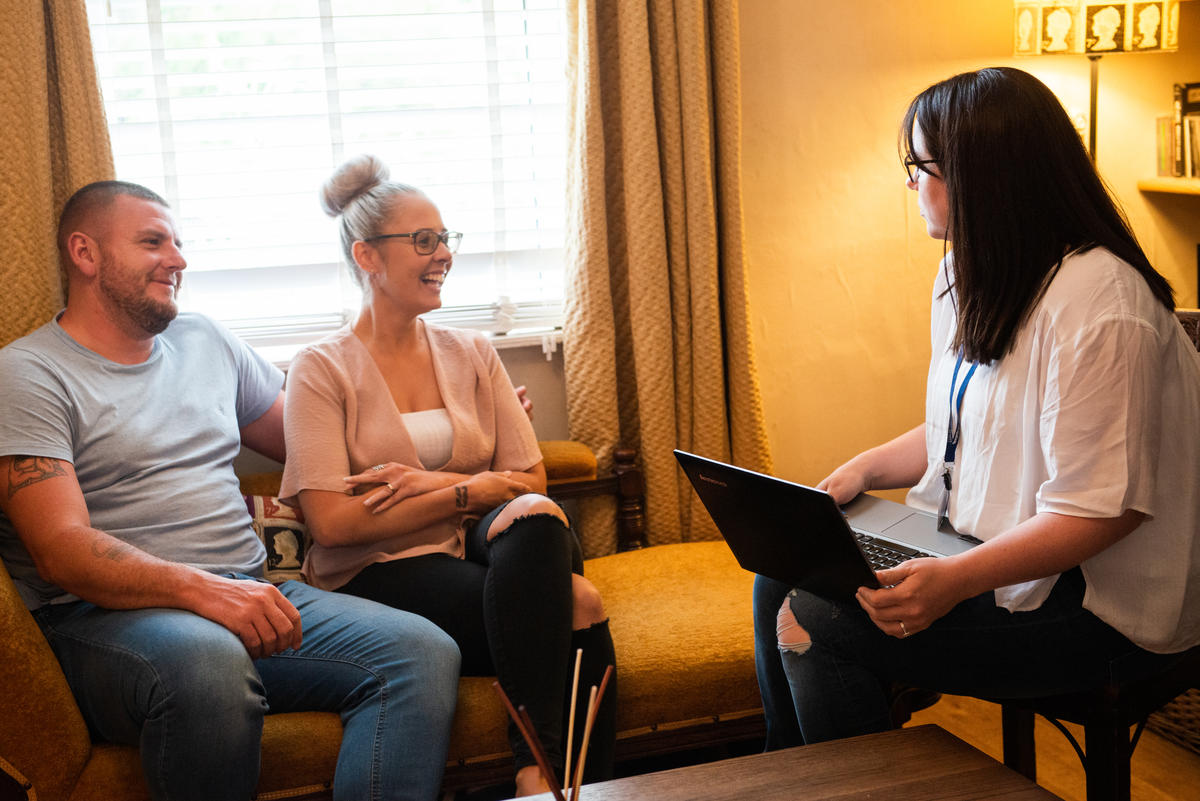 Two parents sat at home chatting to a Together Trust staff member