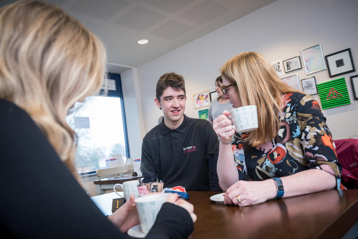 An Inscape student at inCafe, serving two women, enjoying their tea