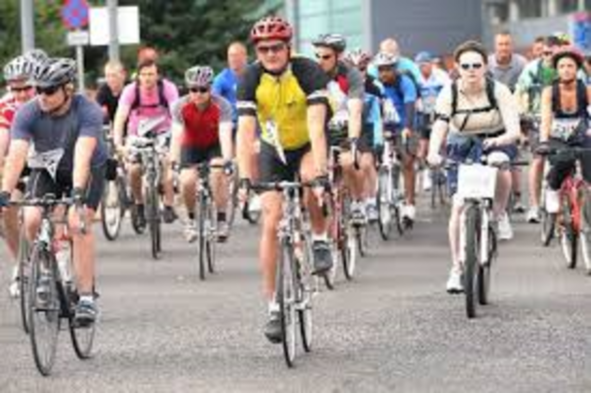 A group of cyclists in brightly coloured shirts riding towards the camera