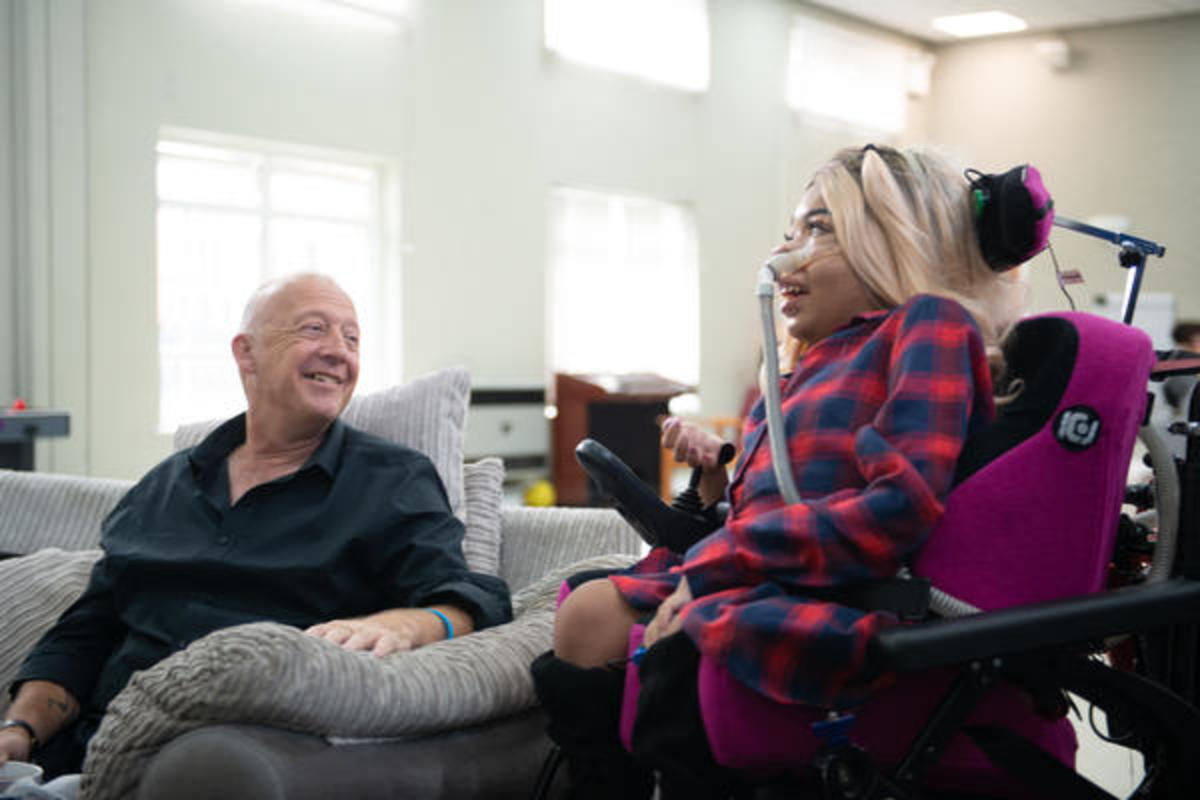 A woman sat in wheelchair talking to a man sat on a sofa