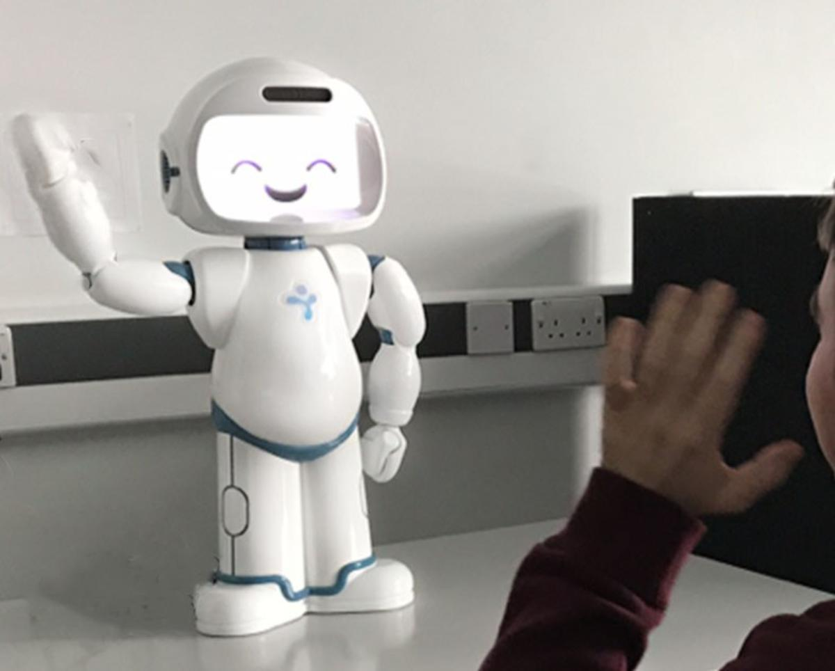 A robot waving with a person waving back at it