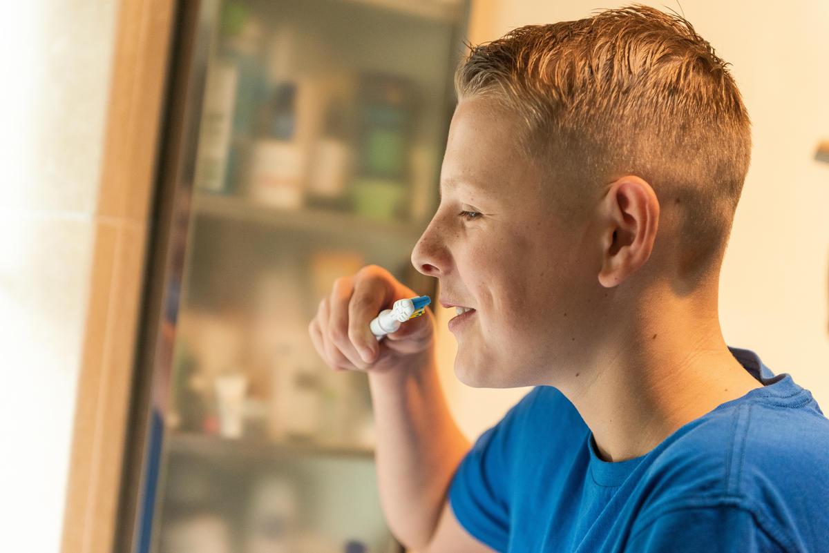 A boy in the bathroom brushing his teeth