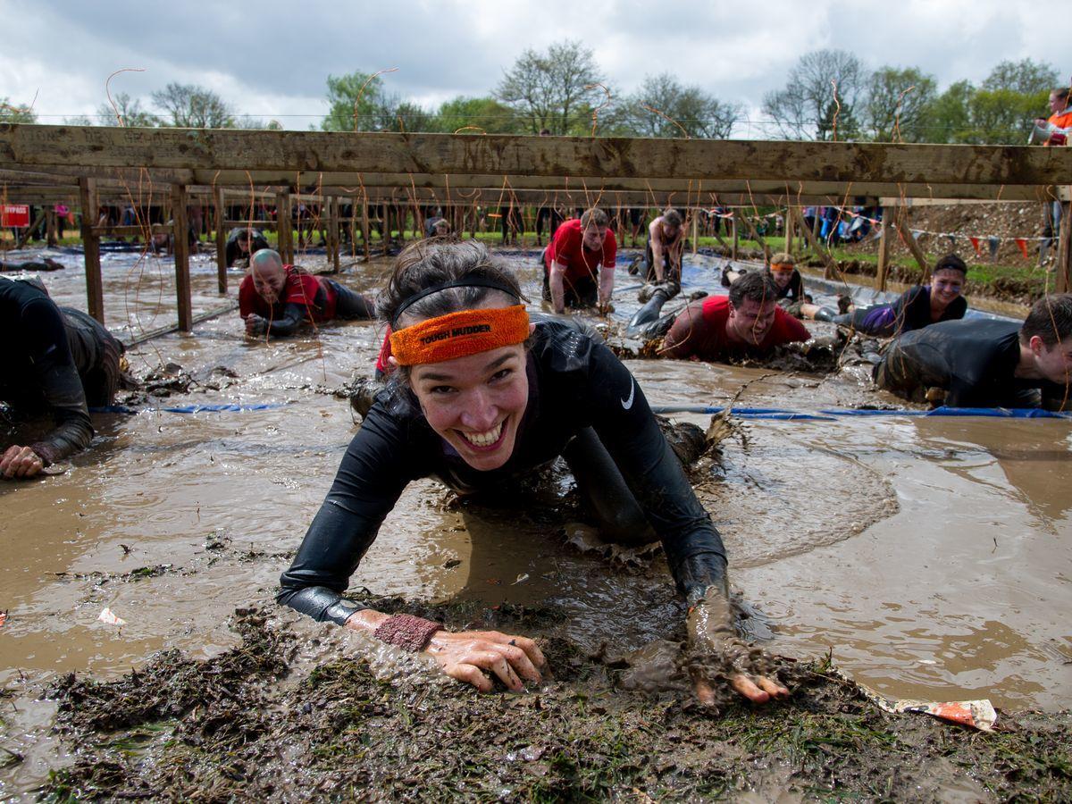 A participant in tough mudder crawling through mud towards the camera