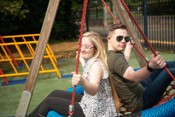 Two young people playing on a swing