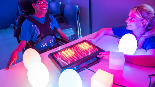 A student at Bridge College playing a sensory activity with lights