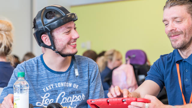 A Bridge College student wearing a helmet and laughing with a staff member