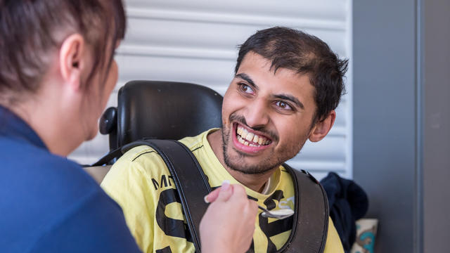 A student at Bridge College in a wheelchair smiling at a staff member