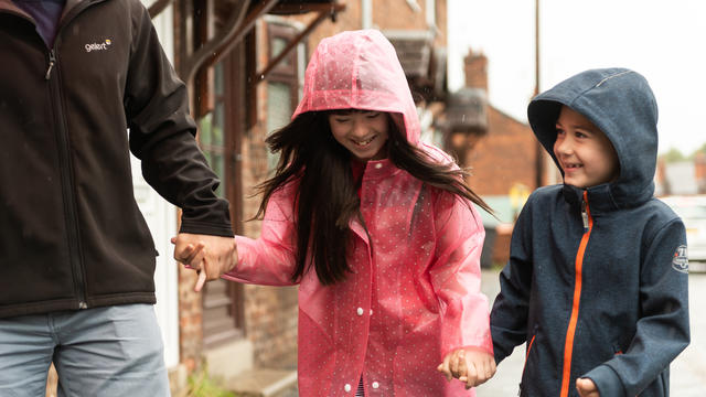 Family walking in the rain, girl smiling