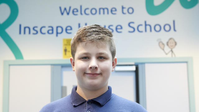 A student stood in from of a sign that says 'welcome to Inscape House School'