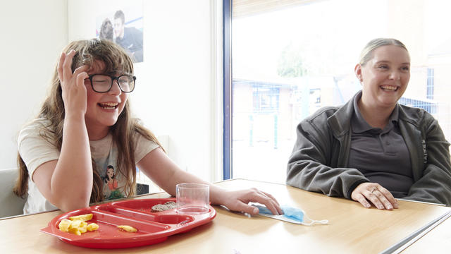 A Inscape student laughing with a member of staff whilst eating their lunch