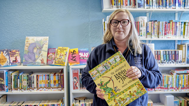 A member of staff holding a large yellow book smiling at the camera stood in front of a bookshelf