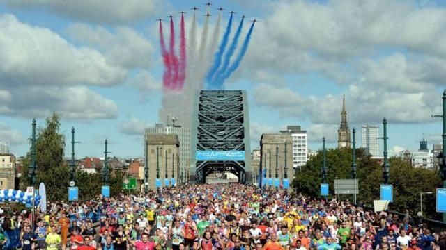 Hundreds of people running in the great north run with the red arrows flying above them