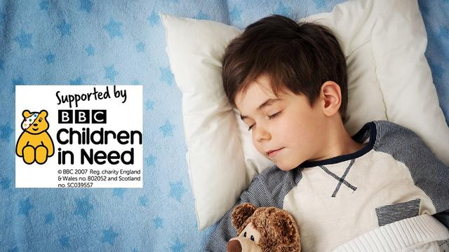 A boy sleeping with a teddy in bed with Children in Need logo