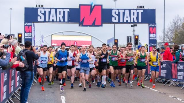 A group of runners setting off on the Manchester marathon in brightly coloured shirts