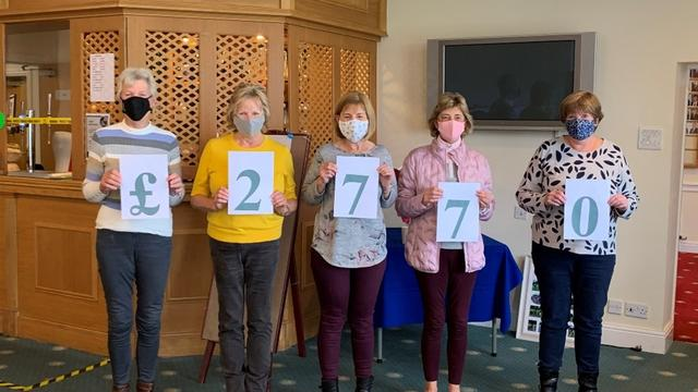 Members of Marple Golf club holding up the total that they raised in numbers