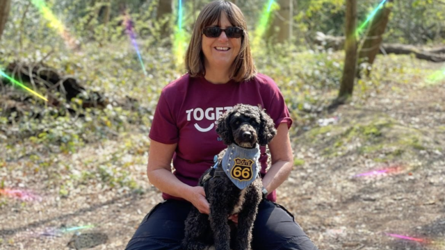 A woman wearing a purple together trust t shirt with a dog sat on her lap