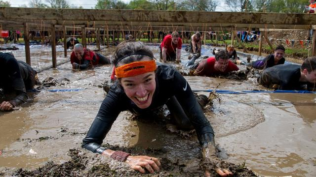 A participant in tough mudder crawling through mud towards the camera